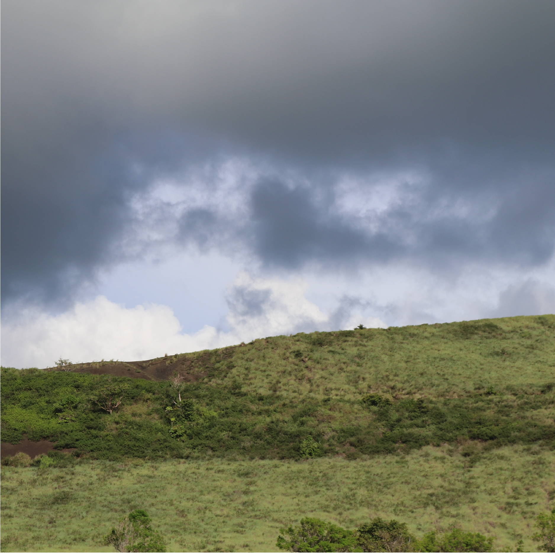 A large green hill in Nicaragua contrasts a dark stormy sky.