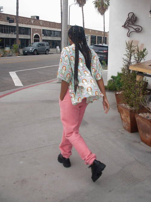 Photo of woman with braids walking away from camera, wearing an anime print Sandy Liang button up shirt and pink Brain Dead sweatpants.