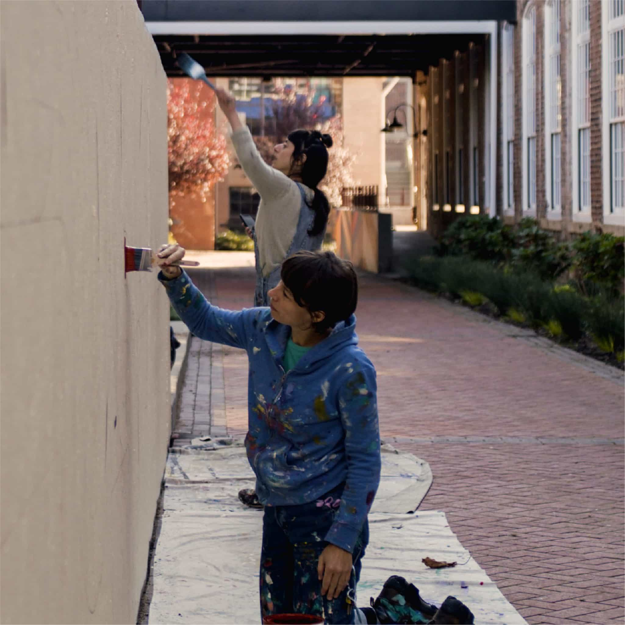 Jessie & Katey painting mural on wall