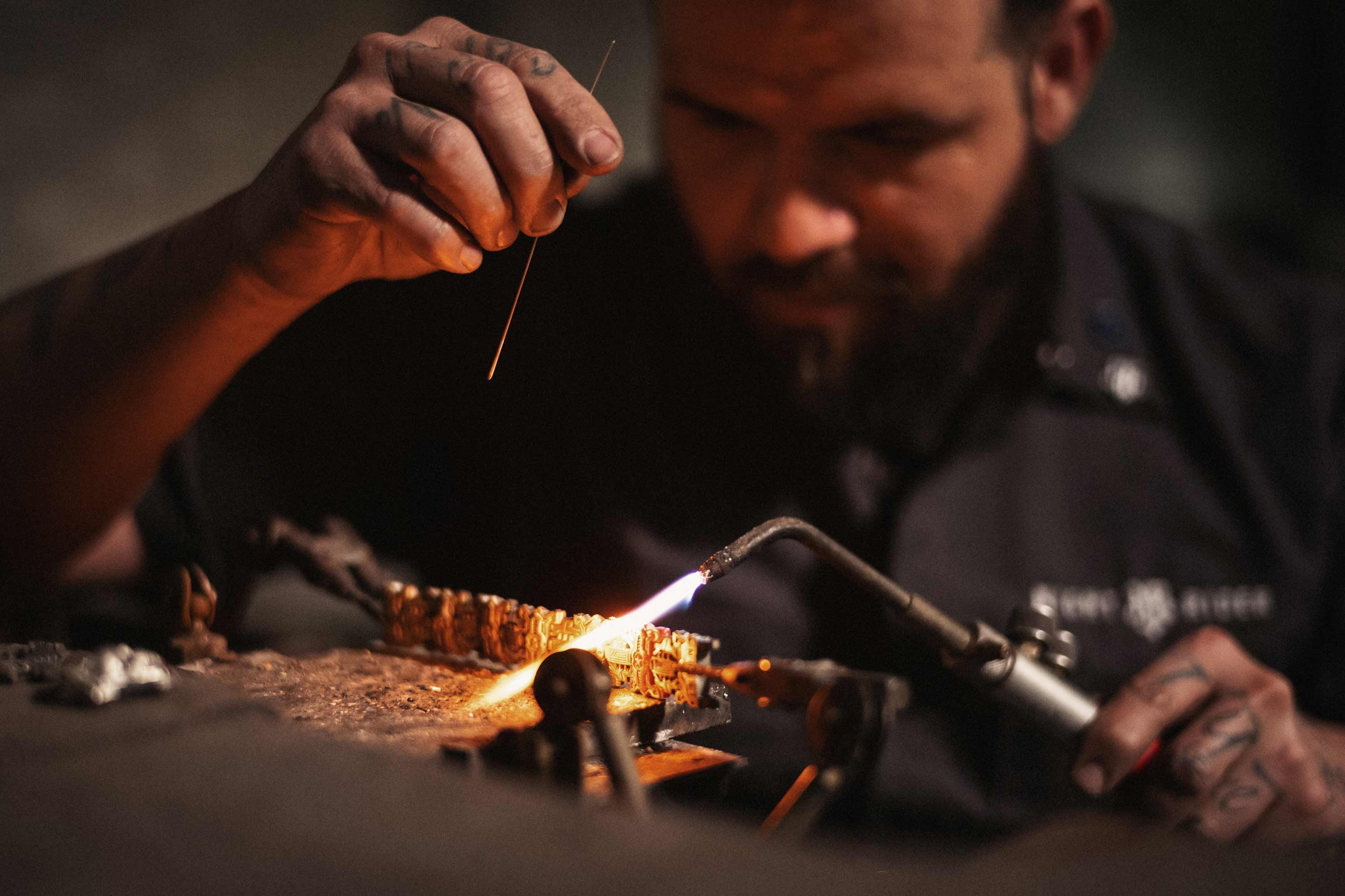 A bench jeweler uses a torch to weld a bracelet