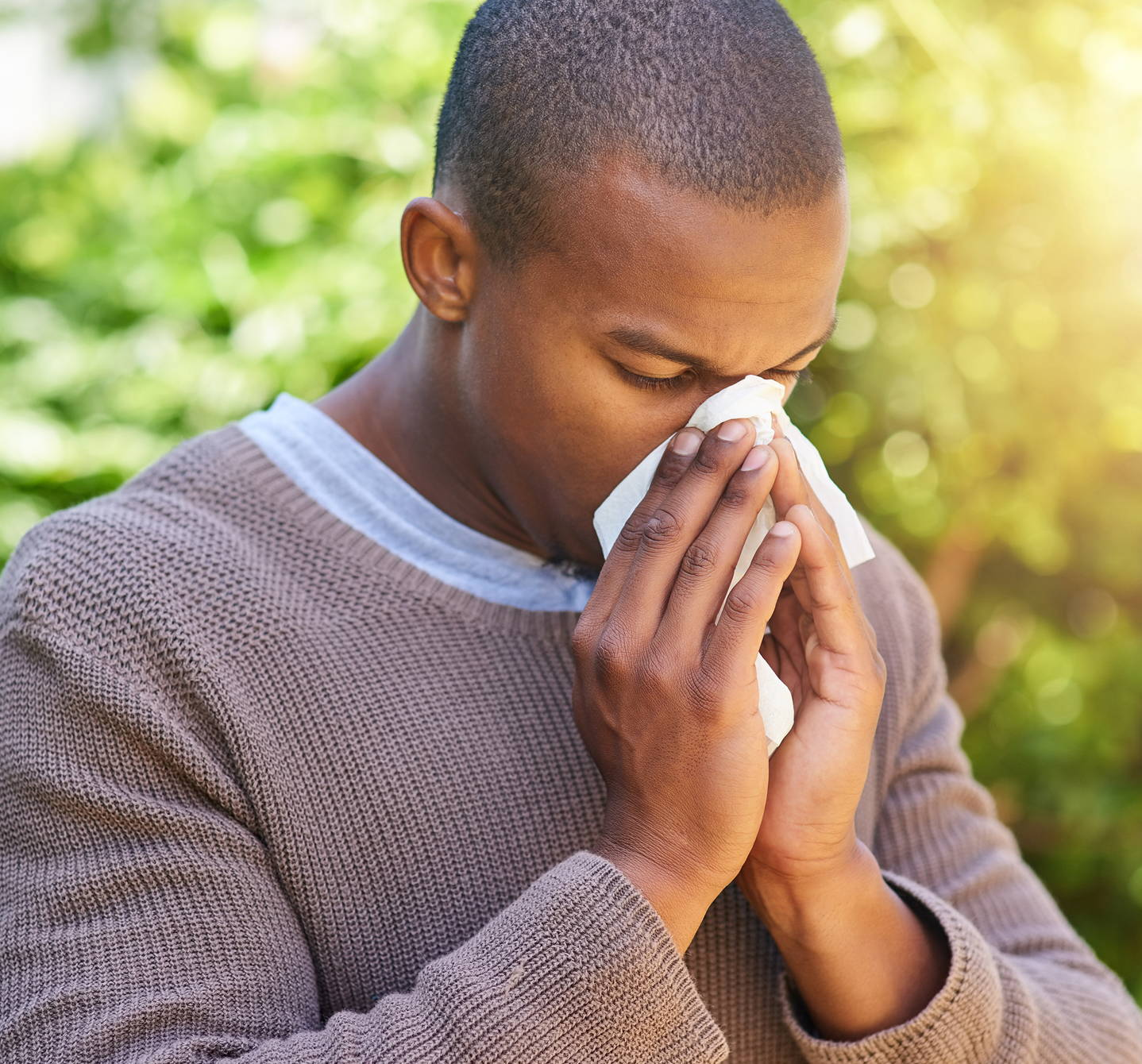 Young man with blowing his nose because of allergies