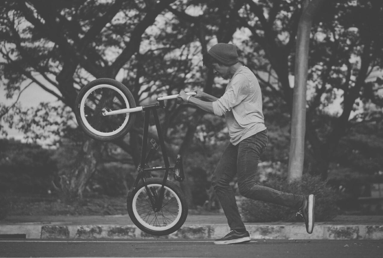 A guy doing tricks in his bicycle in black and white