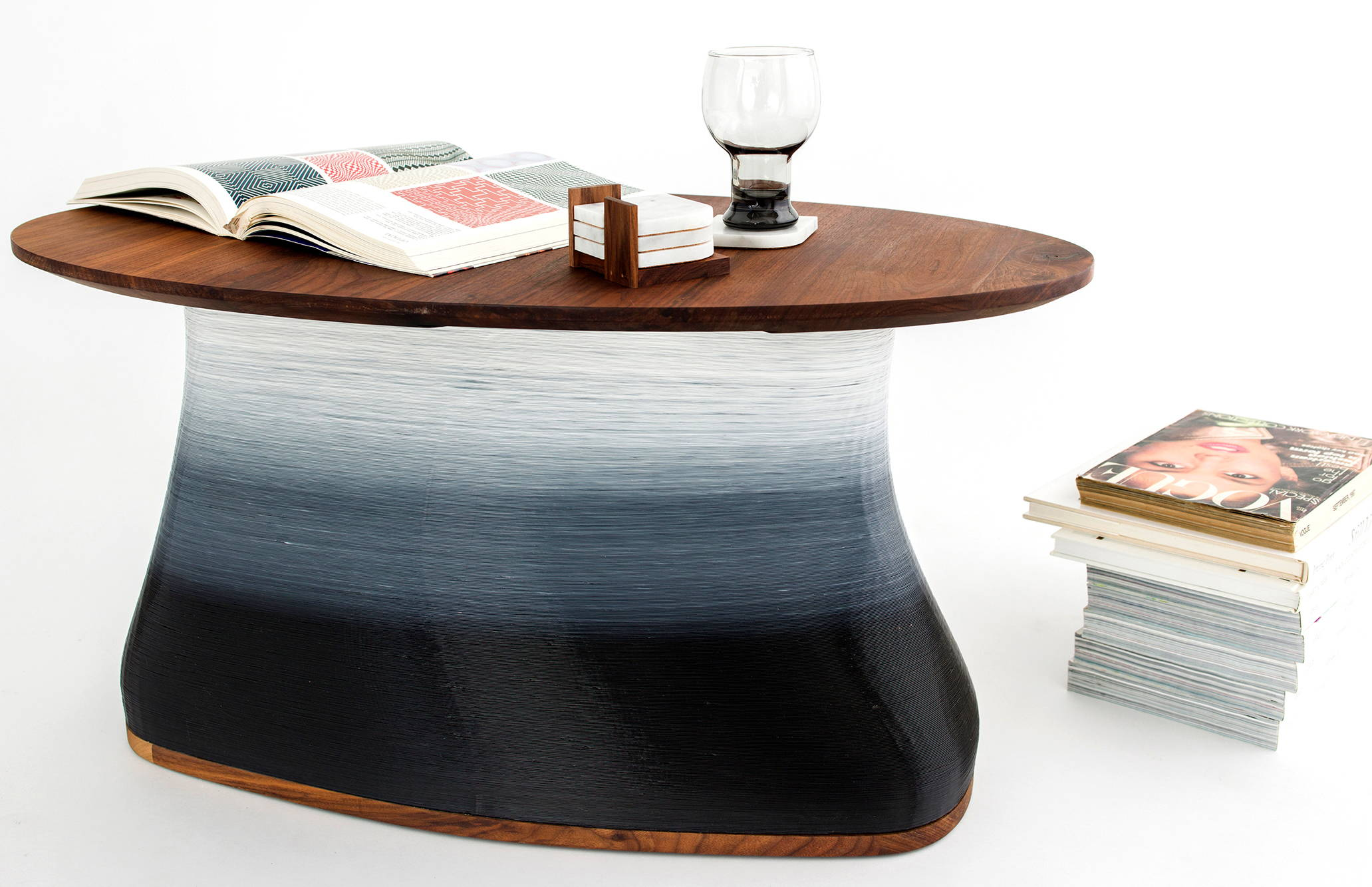 Oval shaped coffee table made of black ombre plant resin base and hardwood top with open book, coasters and glass on surface