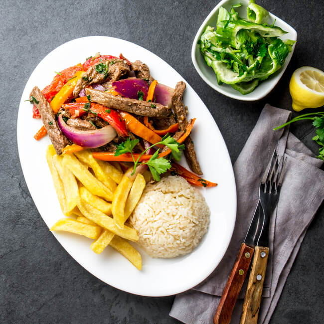 peruvian chinese food - lomo saltado on a plate made of beef stir fry with fries and rice
