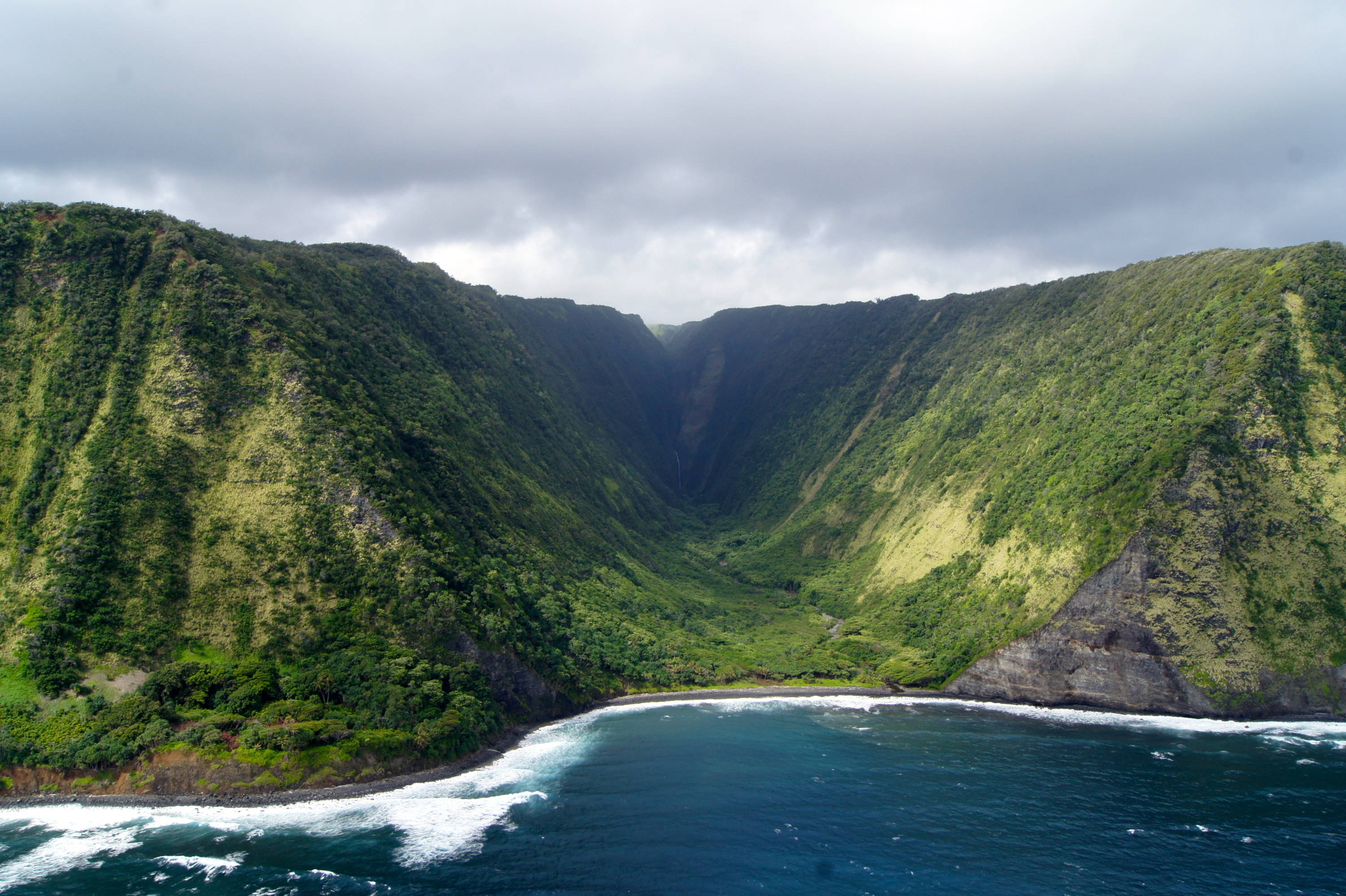 Kona & the Big Island of Hawaii: Things to Do & See. Stark blues and greens juxtapose as mountains give way to valley that leads to a waterfall on Hawaii's Big Island.
