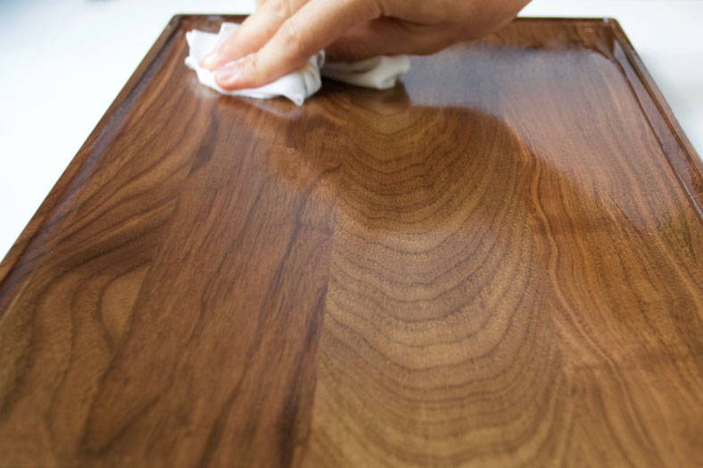 wiping off excess oil after seasoning a walnut wood cutting board with all natural seasoning oil