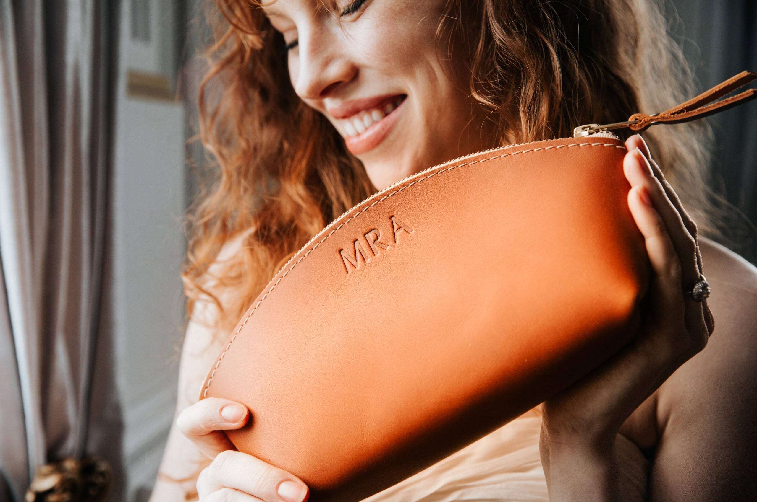 smiling bride holding a handmade leather makeup bag in front of her smile