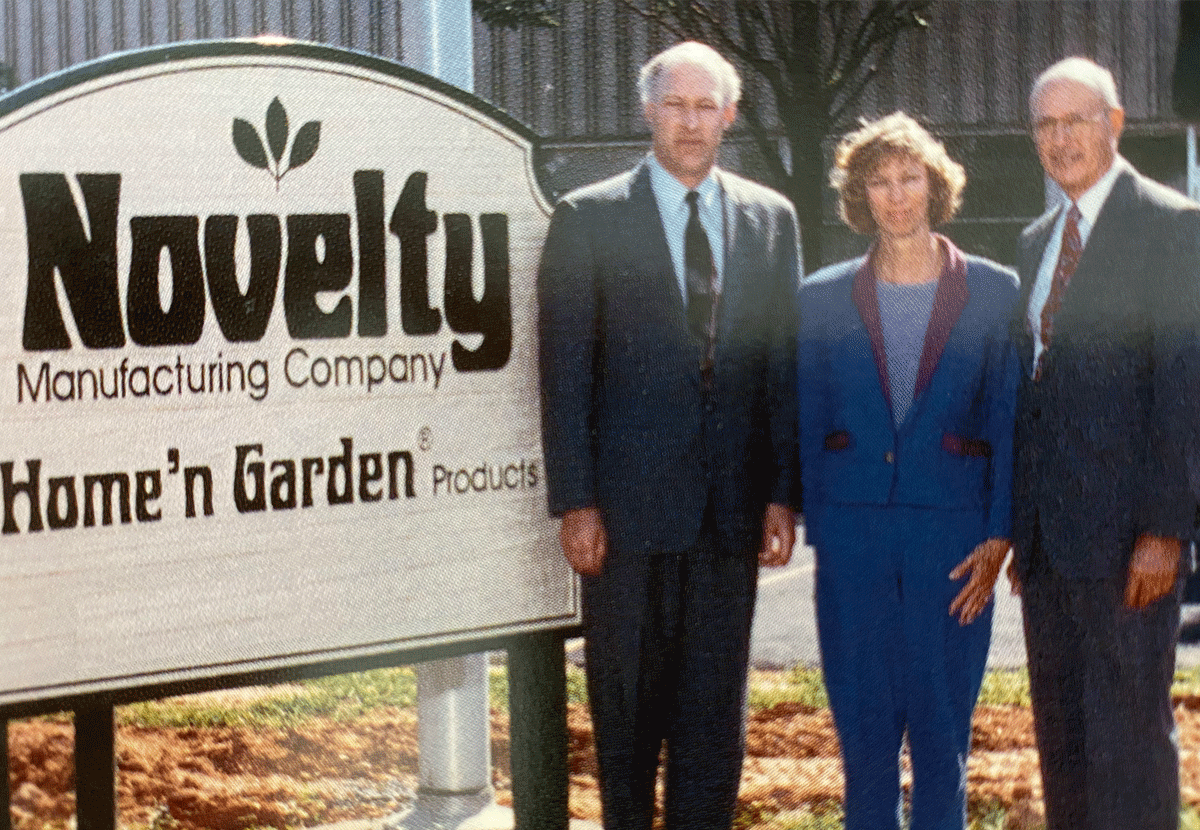 Photograph of Bill Jr., his son Timothy Winger, and Tim's sister Melinda Winger next to company sign