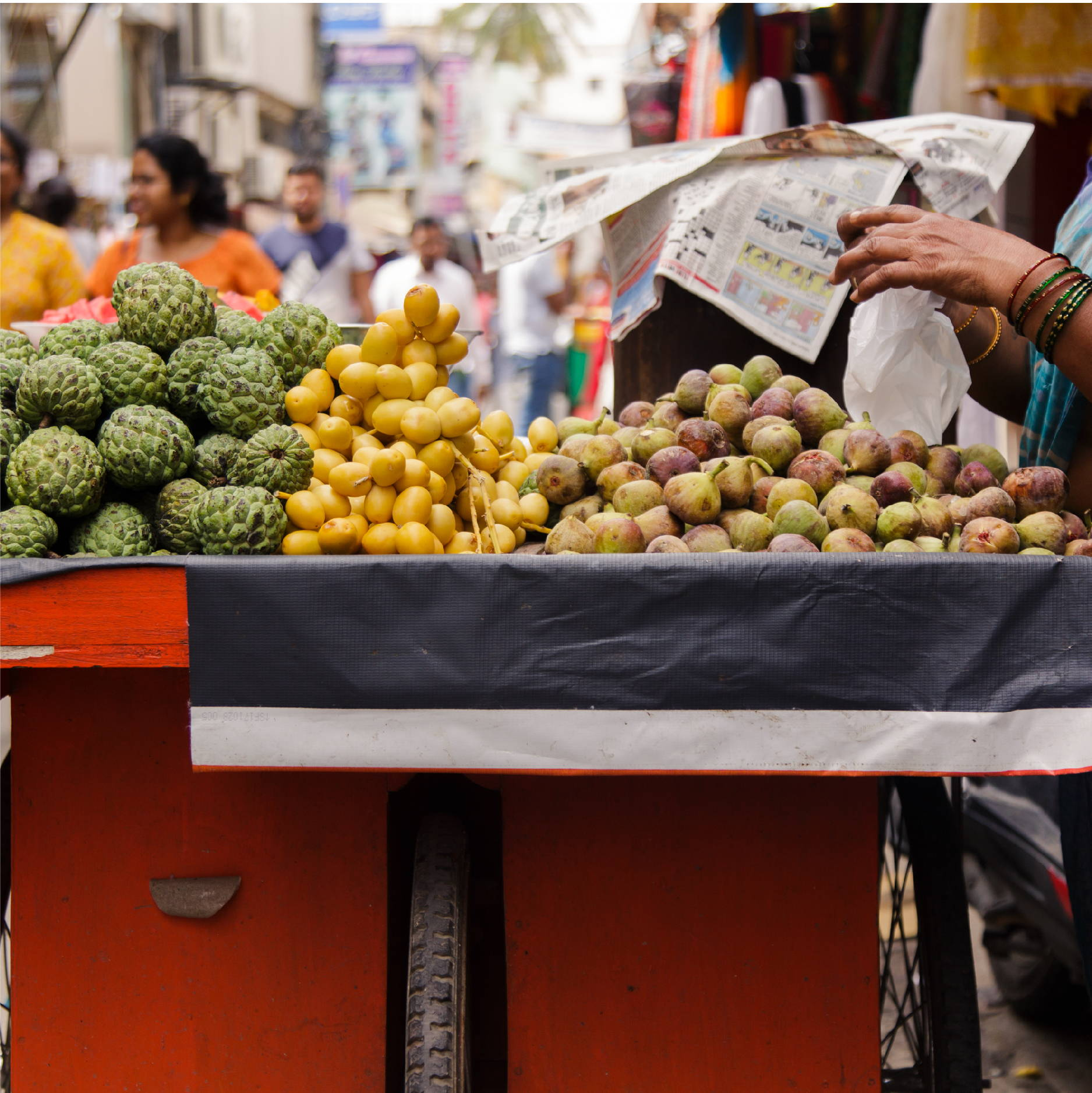 A street vendor on a crowded Bangalore India street, serves ripe figs, dates, and other fruits from her red bike-drawn cart
