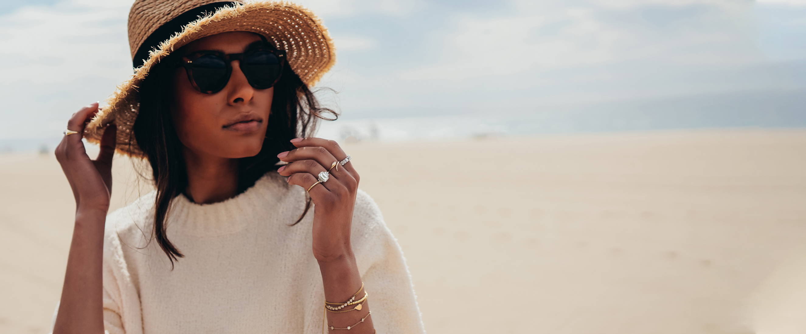 Model wearing beach hat and sweater on the beach in Ring Concierge jewelry