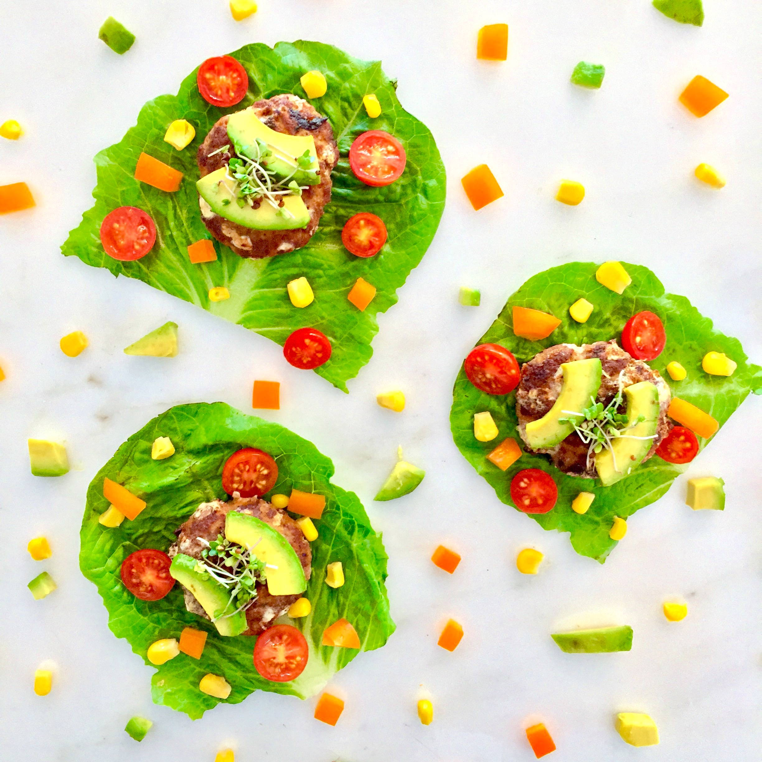 Lettuce cups with cut peppers, corn, tomatoes, turkey patties, avocado and broccoli microgreens.