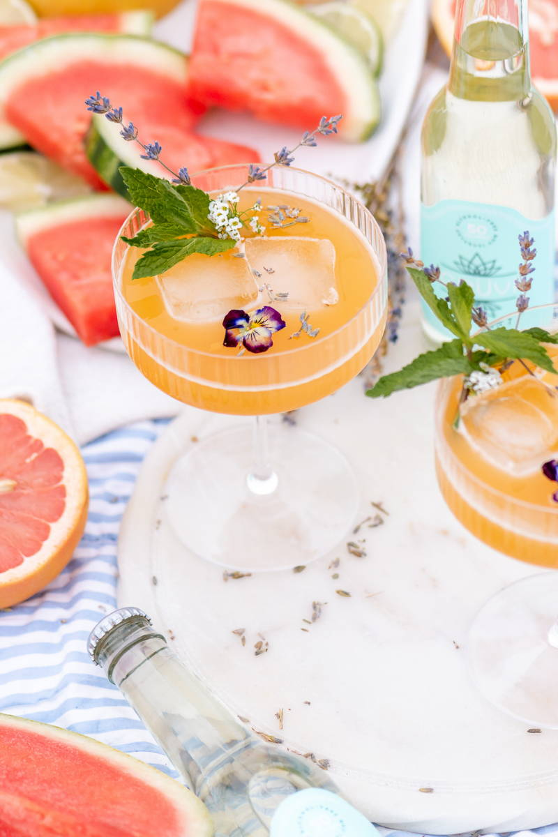 Peach mocktail in coupe glass, topped with pansies and herbs. It is placed on a tray with watermelon and grapefruit.