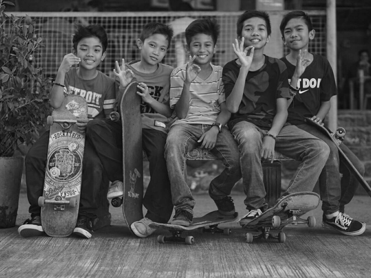 five kids posing with their own skateboard