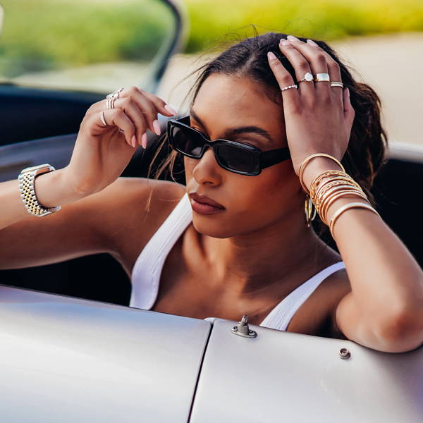 Model wearing Ring Concierge fine jewelry leaning on vintage car.