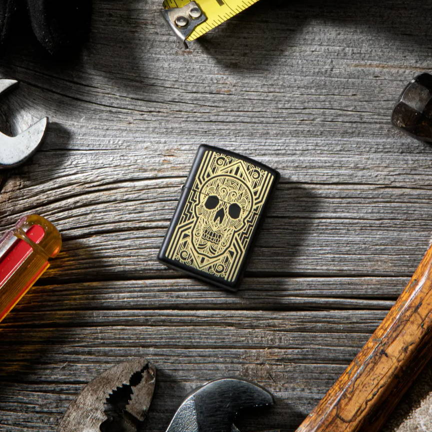 Art Deco Skull lighter, laying on a desk with tools surrounding it