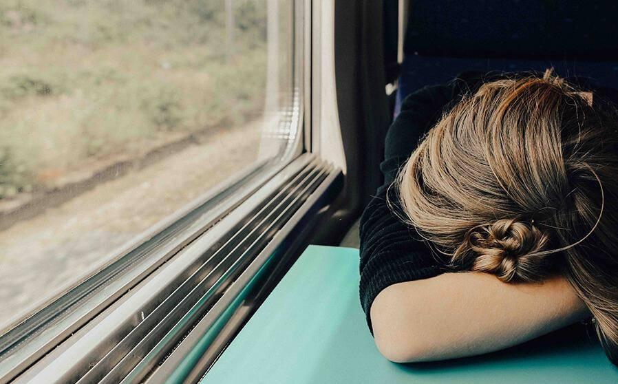 Müde Frau mit Jetlag im Zug