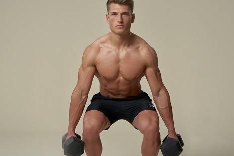 Mann macht Kniebeugen mit Kurzhanteln