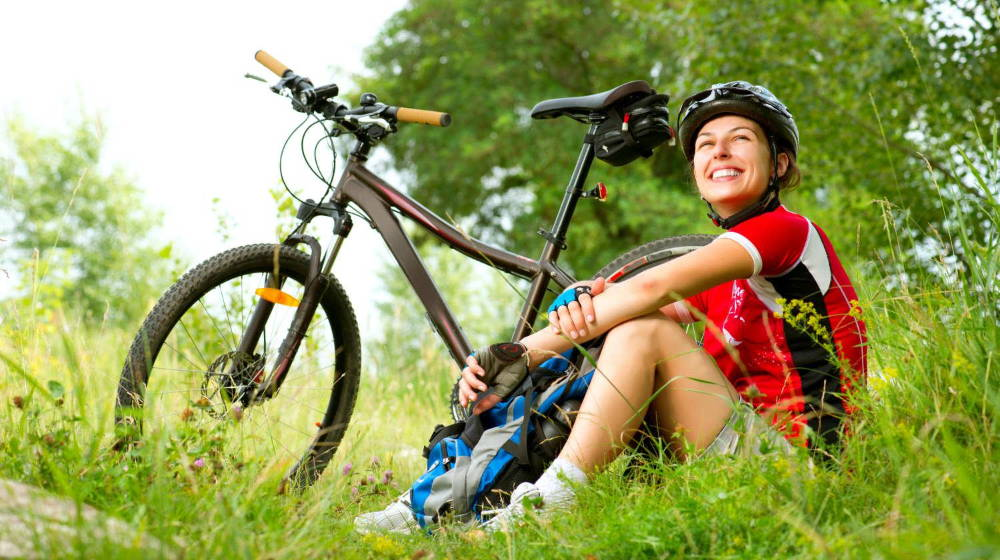 Happy Young Woman riding bicycle outside | Best Natural Antibiotics For Your Gut And Overall Health | best natural antibiotic | Featured