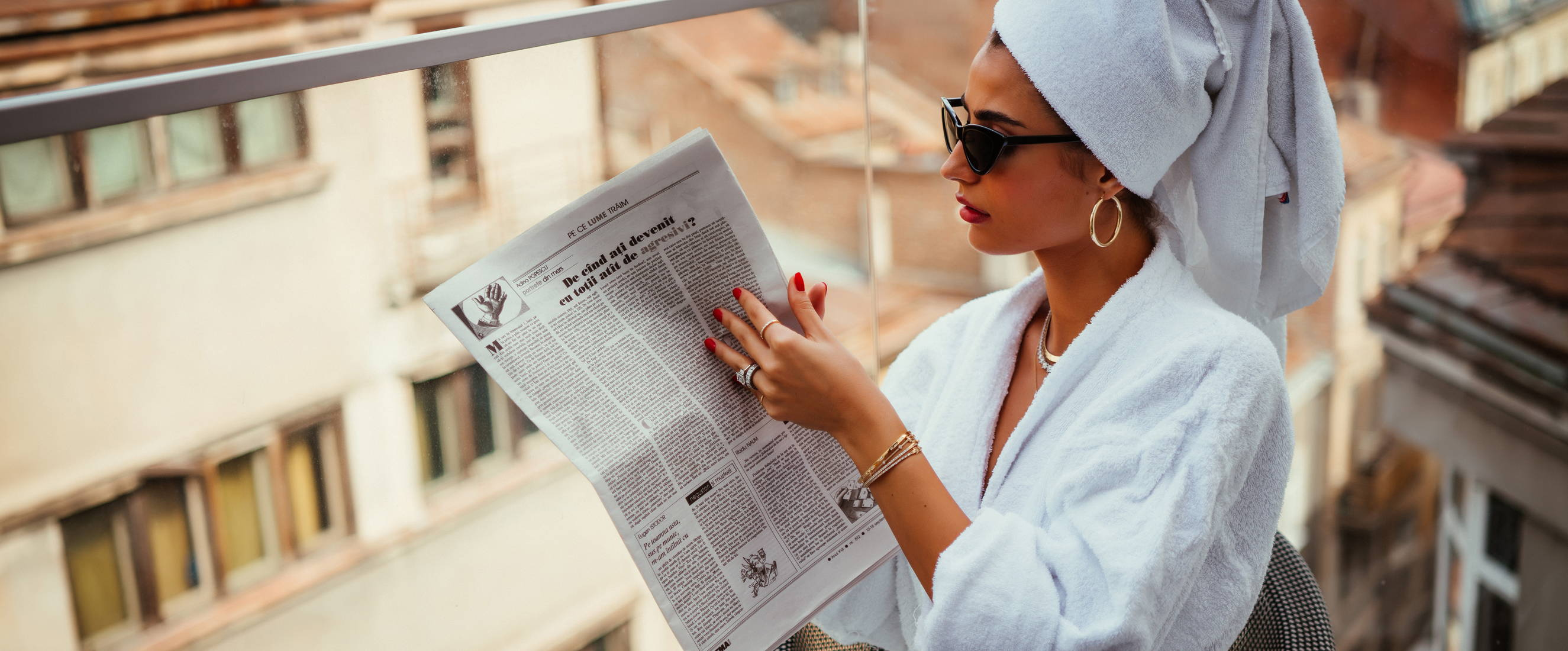 Model wearing Ring Concierge jewelry reading the newspaper.