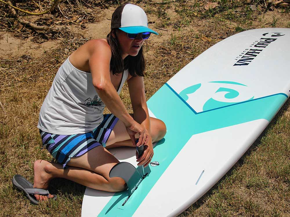 A girl screwing fin hardware into the Big EZ Hawaiian stand up paddle board