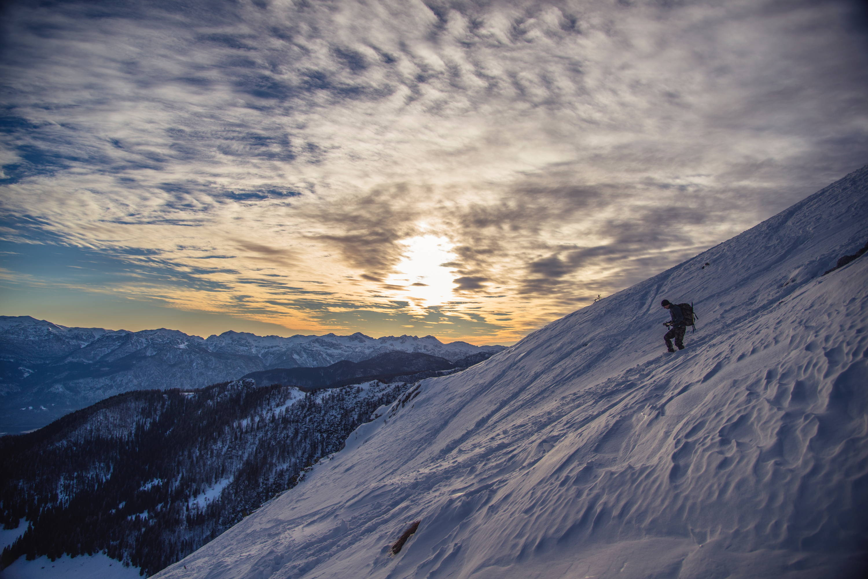 Preparing for High-Altitude Travel: How to Deal with Altitude Sickness. Man descends down snow-capped mountain with sun setting over full range in the background.
