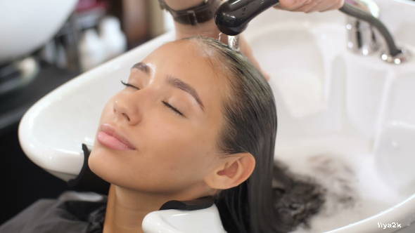 A woman gets her hair washed at the salon
