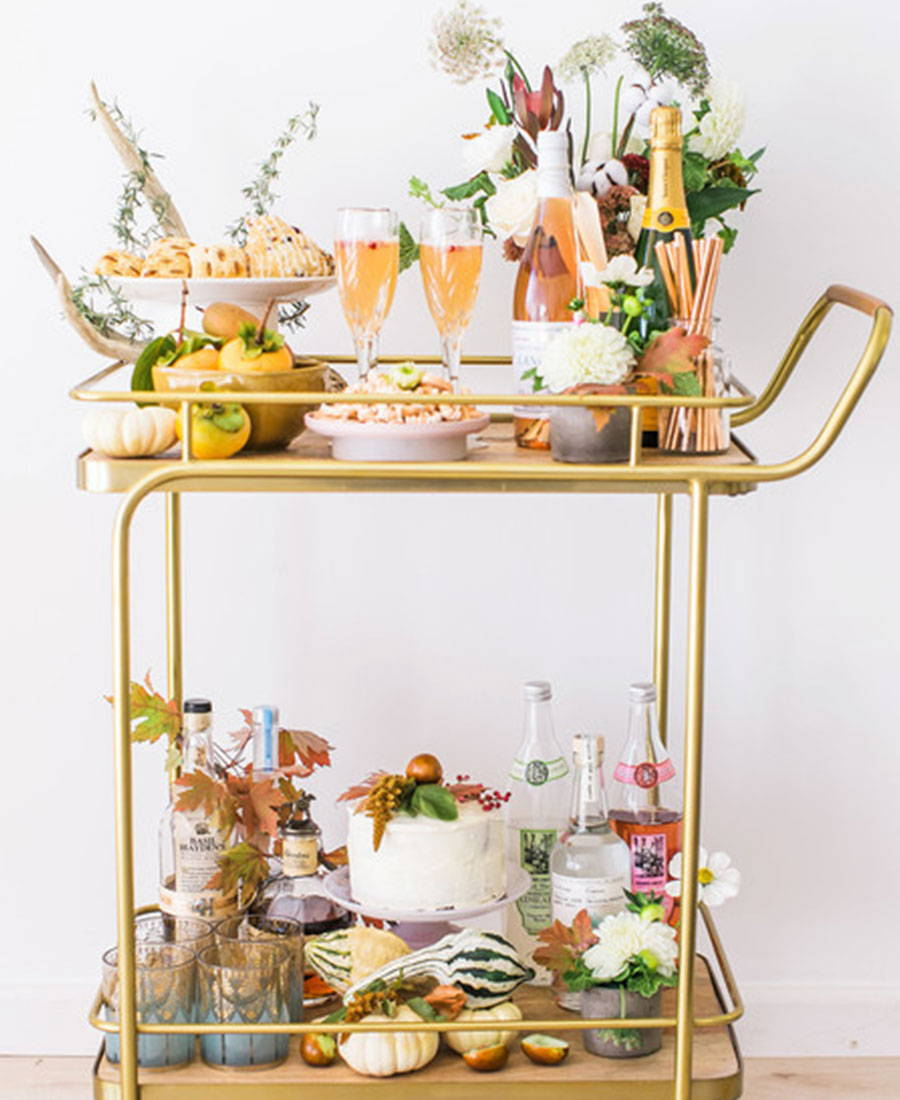 A gold bar cart with champagne, flowers, fruits and cake.