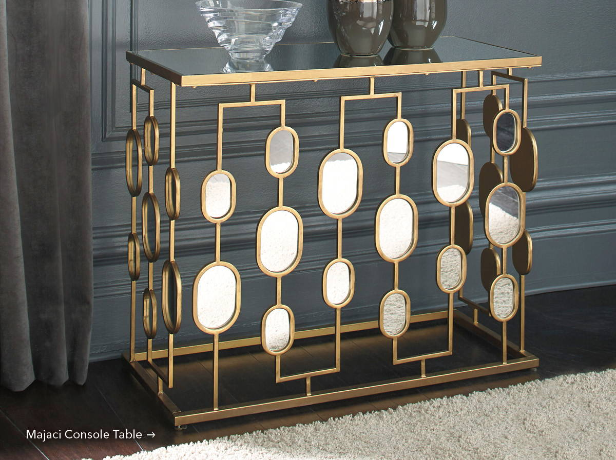 Gold metallic console table or bar with oval mirrored accents. Shop the Majaci.