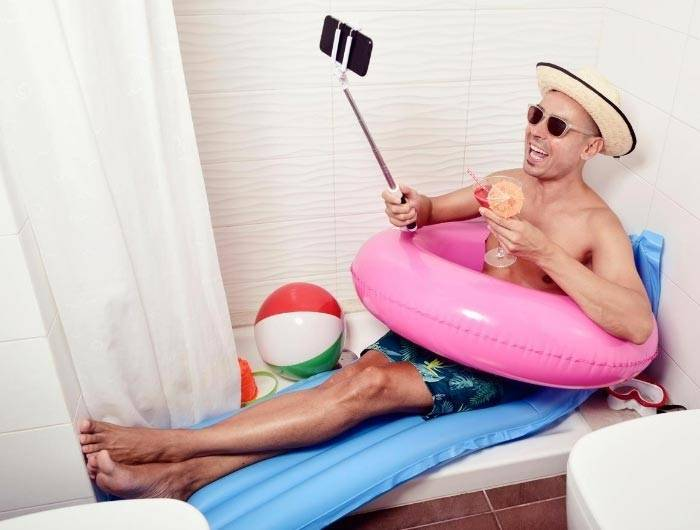 Man in bathtub wearing bathing suit pretending to be on vacation