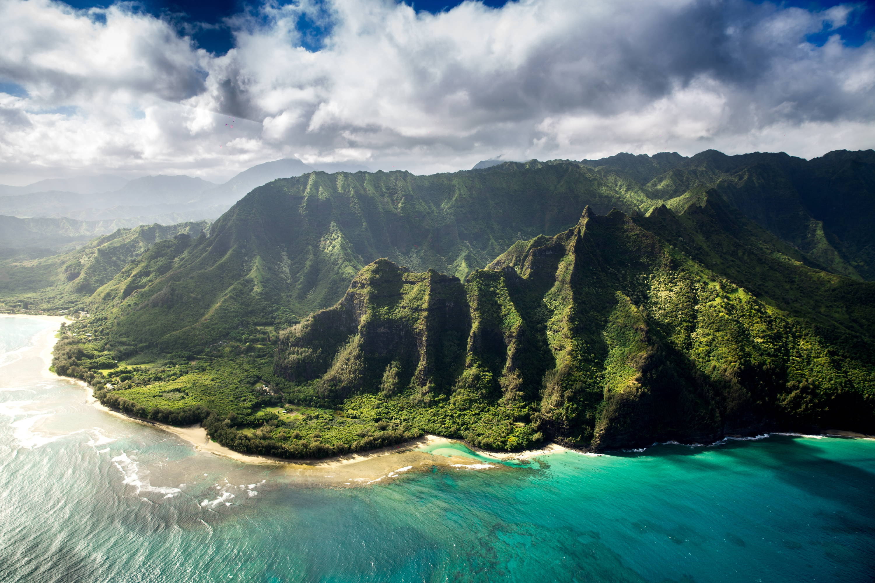 Things to Do in Kauai: The Garden Island of Adventure. Helicopter view of the Na Pali Coast with bright green foliage in the distance, turquoise water below, and blue sky with clouds above.