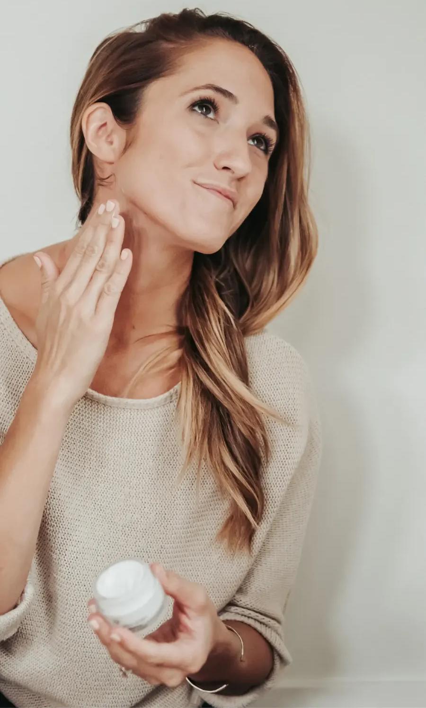 Woman applying Truly O2 oxygen face moisturizer to neck