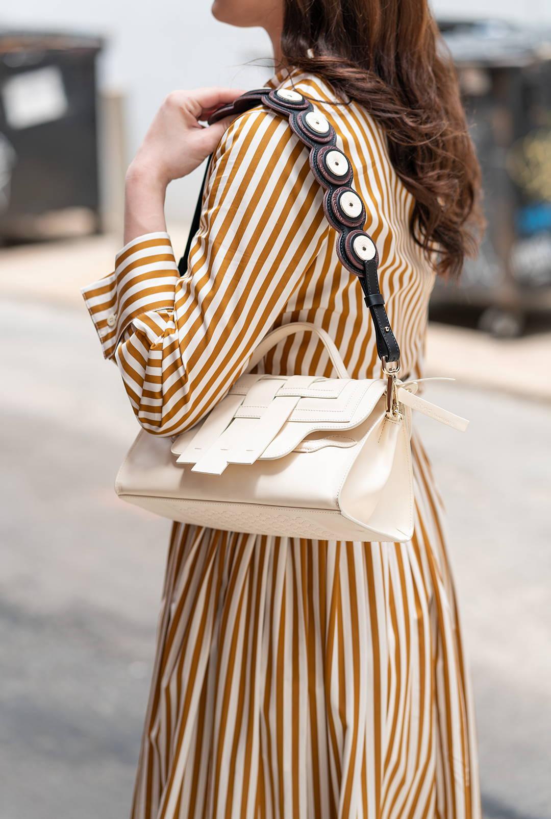 Woman holding cream woven Nina bag by Zanellato