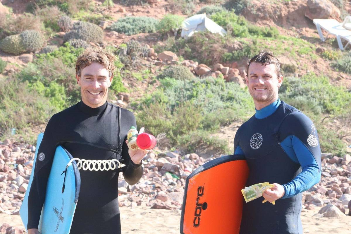 Two surfers picking up plastic litter from the beach