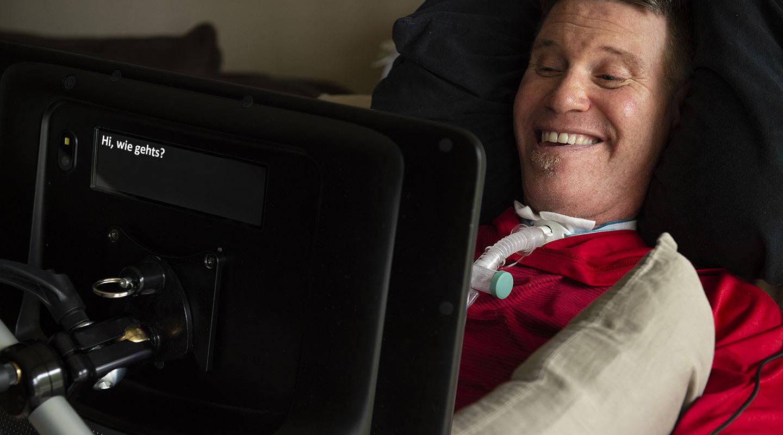 Mann benutzt ein UK-Gerät der I-Serie von Tobii Dynavox zum Kommunizieren