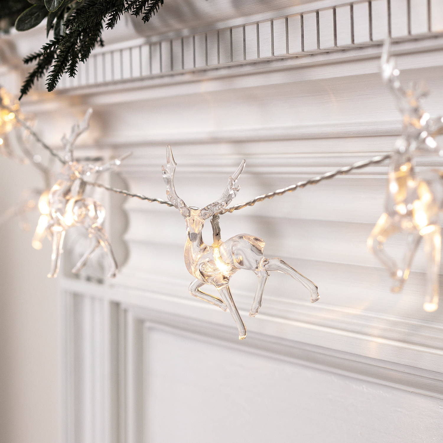 Reindeer battery Christmas fairy lights draped over a  mantle piece