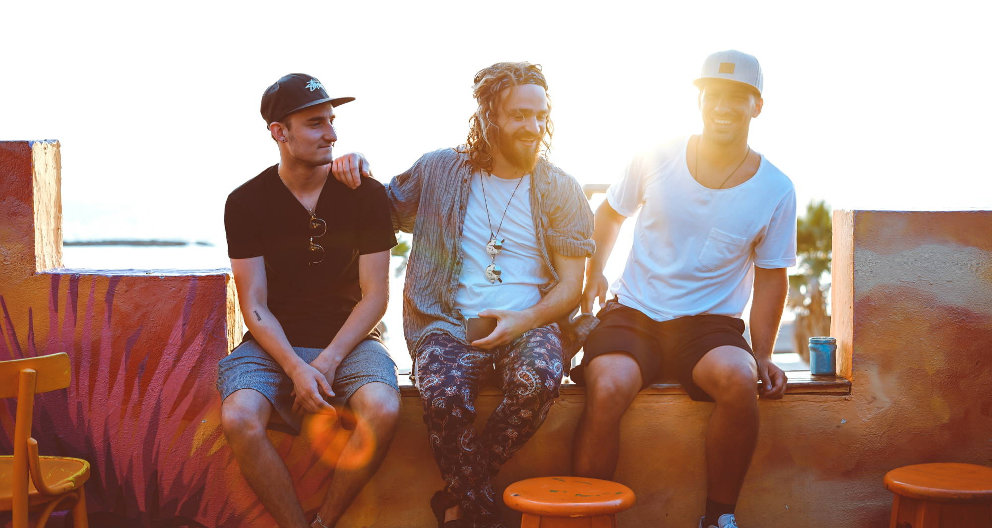 Three men sit on a wall in sustainable mens clothing and talk while the sun sets behind them.