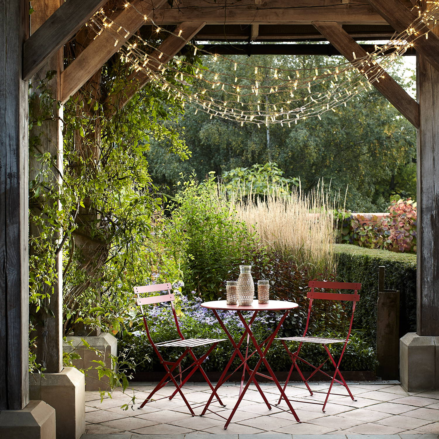 A red table and chair set under a wooden structure with a fairy light canopy above