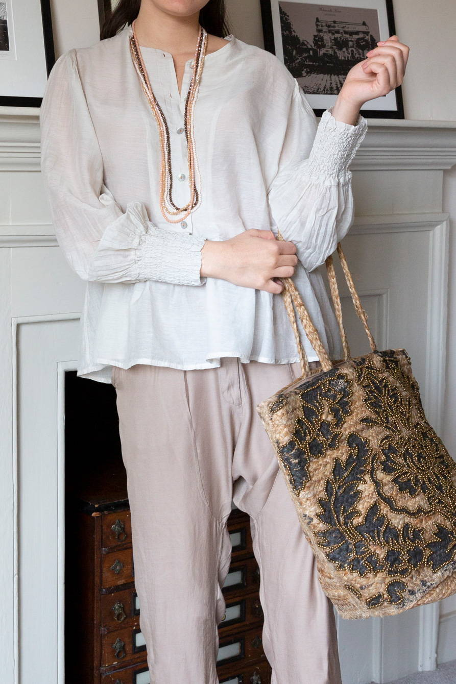 Neutral trousers paired with a silk blouse and crystal necklaces.