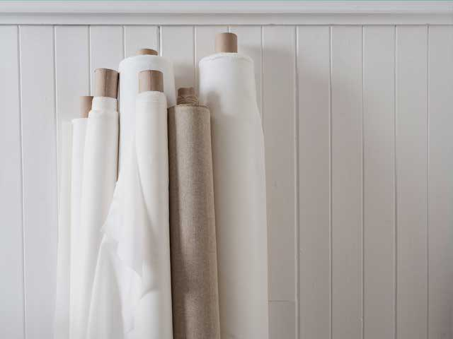 Rolls of plain natural fabrics, Silk, British woven linen, cotton and a silk bamboo, leaning up against a white wall, ready to be printed on using reactive dyes.