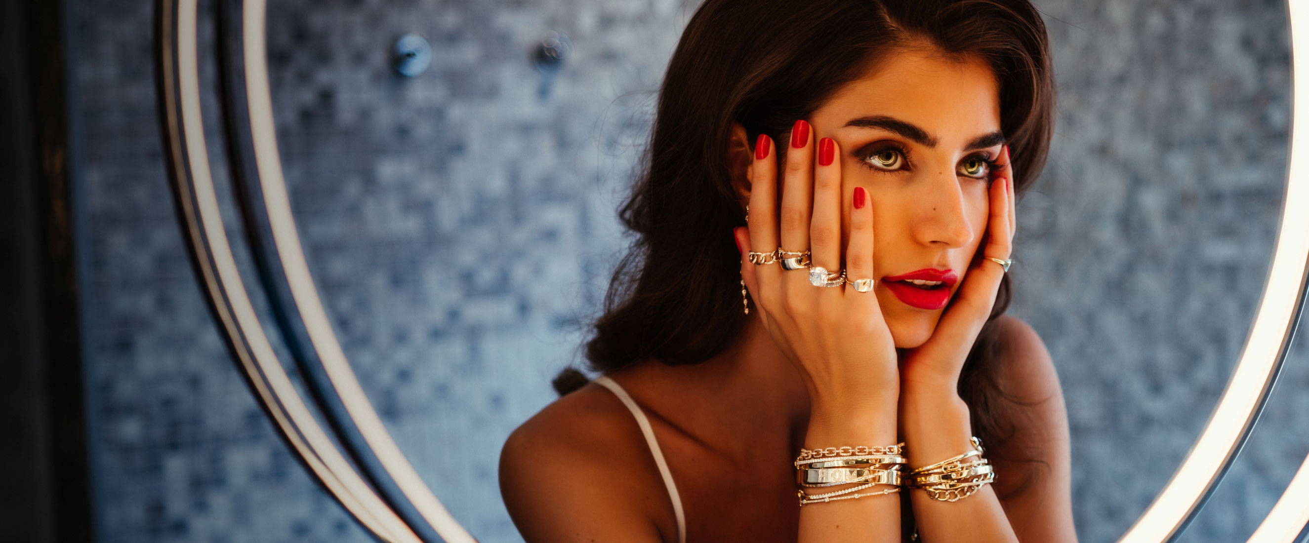 Model wearing Ring Concierge jewelry looking in the mirror