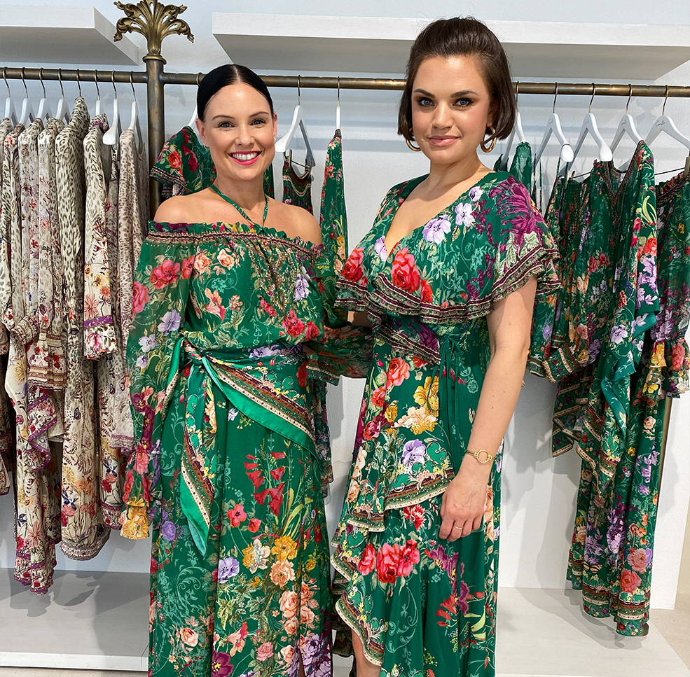 Two CAMILLA Styling Angels wearing Long Rich Green Dresses  with colourful Florals