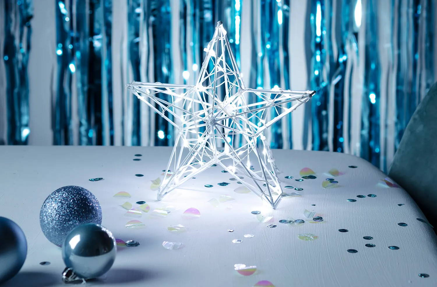 white star battery Christmas light on table top with confetti