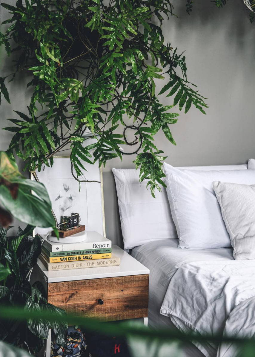 Bed with white eucalyptus sheets with a stack of books