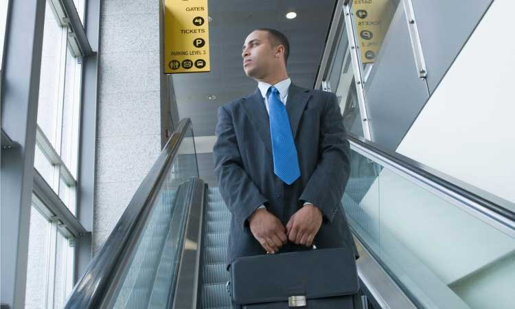 Man wearing suit and blue tie on escalator
