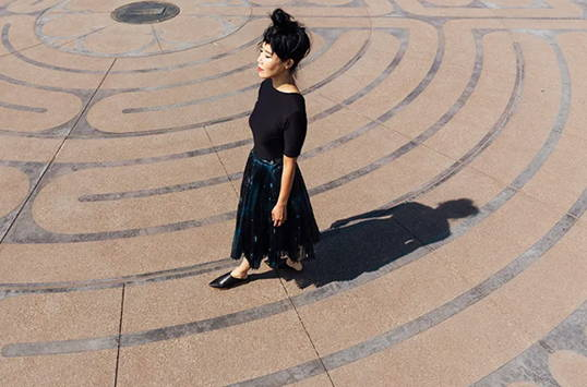 A women in a black dress walking and wearing Vision Quest black shoes