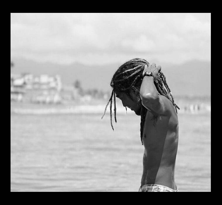 A shirtless guy in the beach fixing his dreads