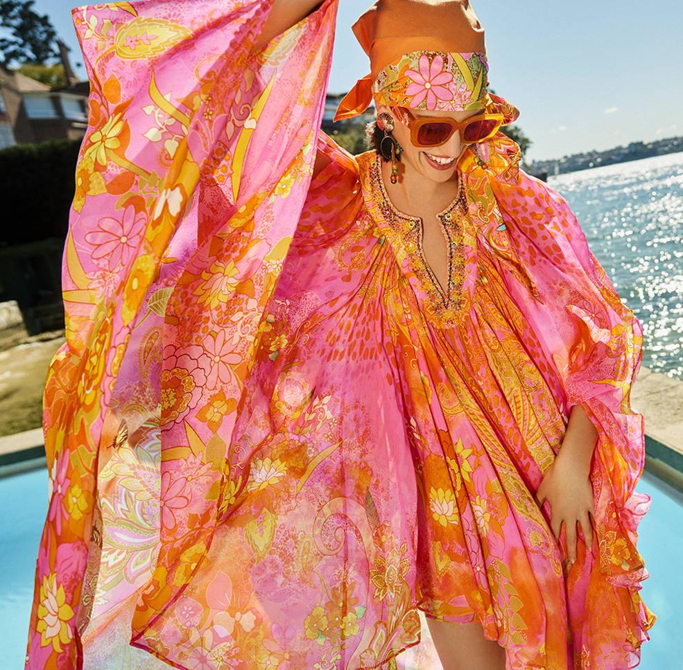Model in CAMILLA fluro orange and pink kaftan by pool