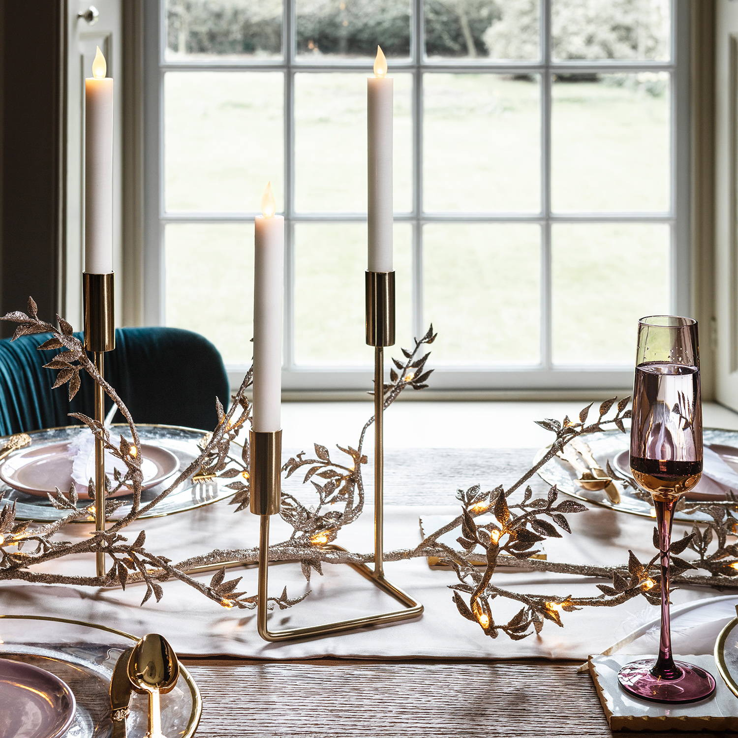 gold candelabra on top of a Christmas table with a matching gold garland