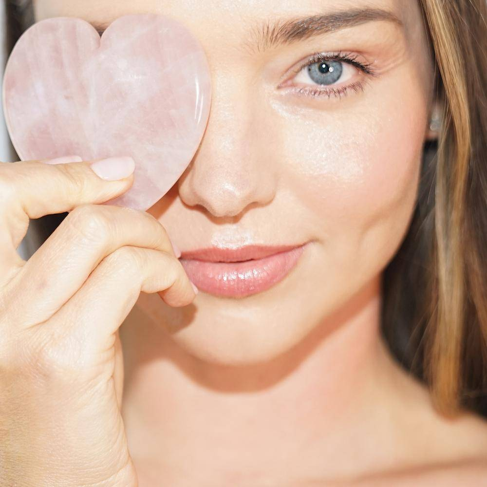 Miranda Kerr covering one eye with the Heart Facial Sculptor