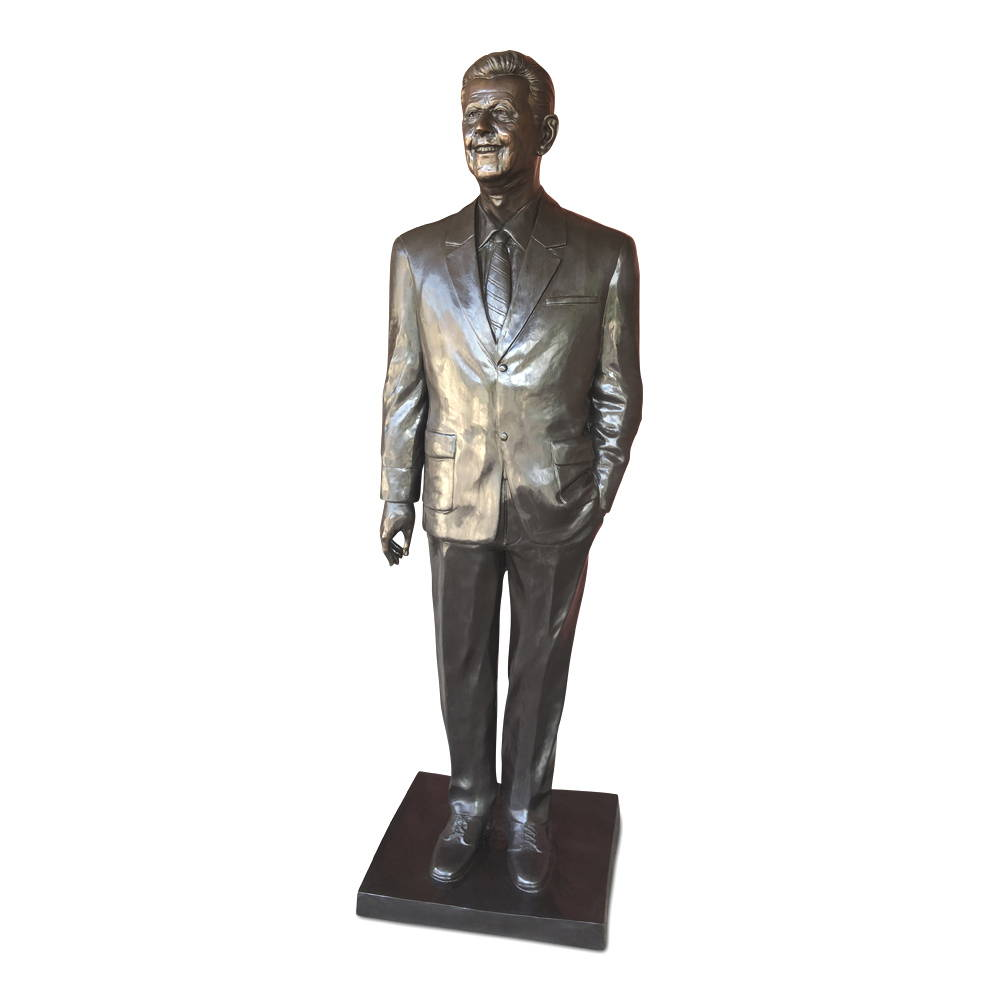 A life-size bronze statue of a man wearing suit with his left hand inside his pocket